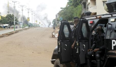 Guinea's security forces watch as smoke billows on a street in Bambeto during a protest after opposition candidates called on Monday for the results of the election to be scrapped due to fraud, in Conakry