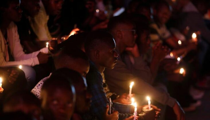 Participants hold candles while holding a night vigil during a commemoration ceremony marking the 25th anniversary of the Rwandan genocide, at the Amahoro stadium in Kigali
