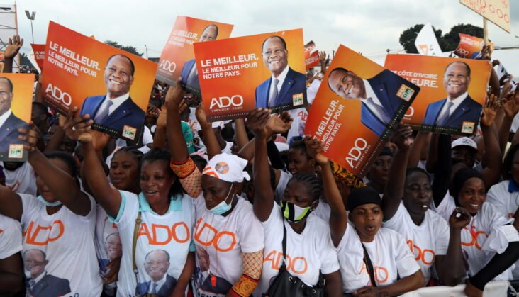 Supporters of presidential candidate Alassane Ouattara of the ruling RHDP coalition party hold signs during a campaign rally for the October 31, 2020 presidential election, in Abidjan